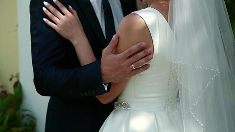 On a wedding day the groom strokes the bride's hand, the wedding bouquet Footage