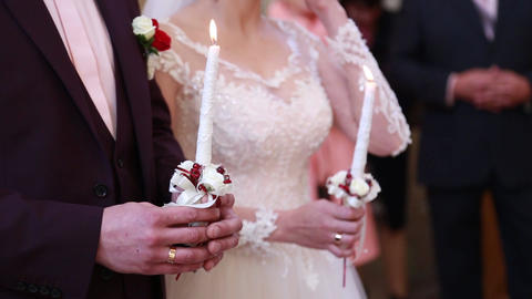 The church, the bride and groom hold candles on the wedding Archivo
