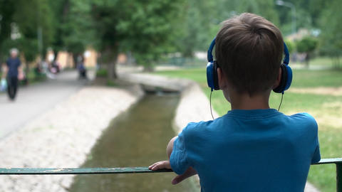 The boy listens to music on headphones Footage