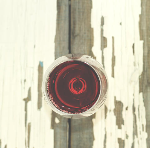 A glass of red wine on a white vintage board Fotografía