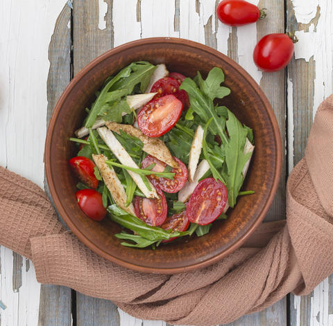 Closeup of delicious salad of arugula with cherry tomatoes and chicken breast in Photo