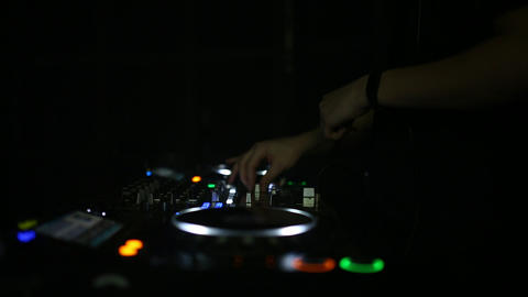 A professional DJ working in a club at a party turns a crowd of people and mixes Live Action