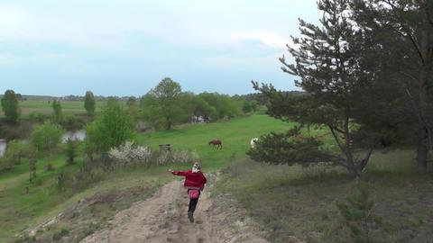 Village little girl runs along sandy path down hillside. Child runs into ビデオ