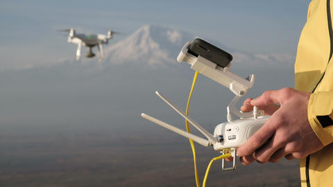 Man hands control flying quadcopter near mountain Archivo