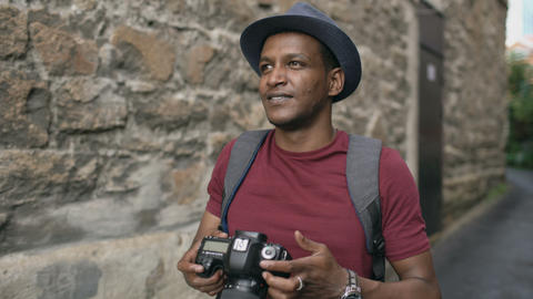 African happy tourist taking photo on his dslr camera. Young man travelling in Footage