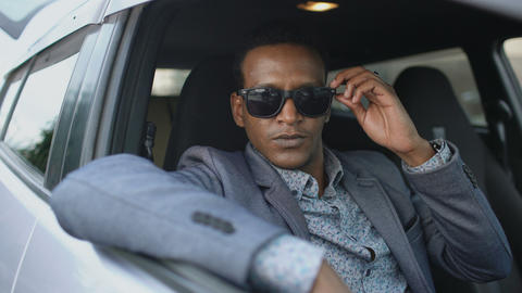 Portrait of serious businessman sitting inside car put of sunglasses and smiling Footage