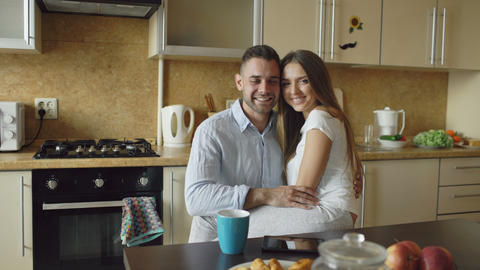 Portrait of happy smiling couple sittting in the kitchen early morning at home Footage