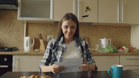 Attractive happy woman recieve good news reading letter in the kitchen while Footage