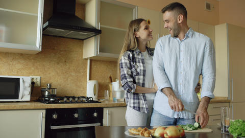 Happy young couple kissing embracing and chatting in the kitchen while cooking Footage