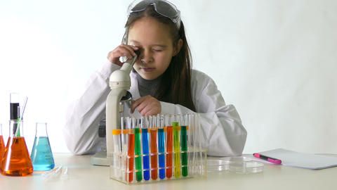 Young scientist checks microascope notes looks at camera Footage