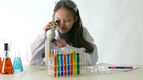 Young scientist checks microascope notes- Footage