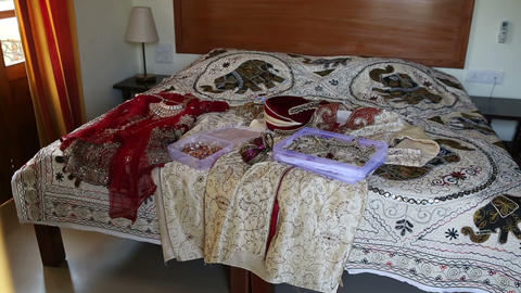 Closeup Large Bed with Indian Wedding Dresses and Jewellery Footage