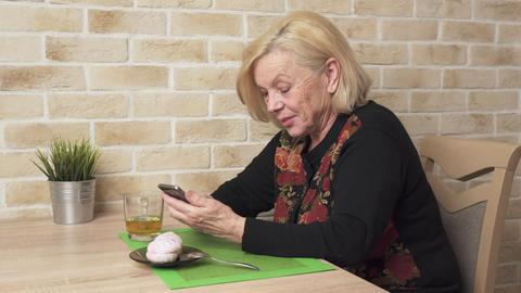 Happy elderly woman using a smart phone ビデオ