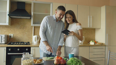 Attractive couple meet in the kitchen early morning. Handsome woman using tablet Footage