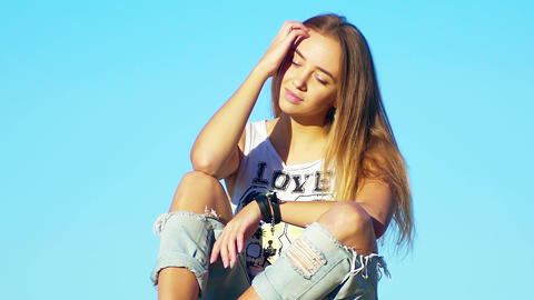 Young beautiful long blonde woman sits in sunlight, closed eyes 영상물