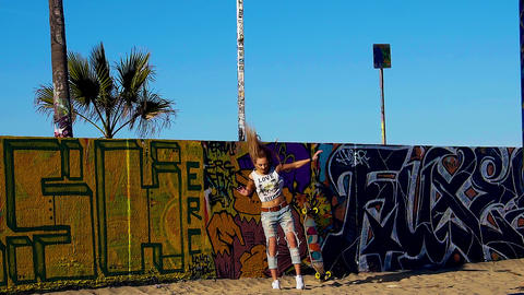 Young long blonde hair woman skater jumping down from a graffiti wall Footage