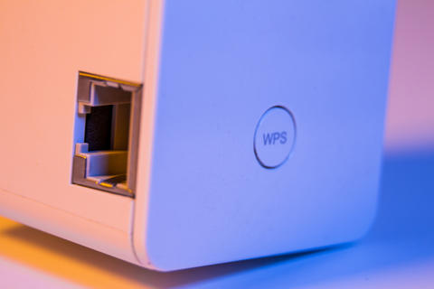Closeup on WiFi repeater WPS button and ethernet socket フォト