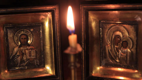 light a candle in front of the icons of Jesus and the Mother of God Footage