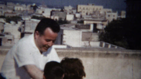 1954: Drunk Italian uncle dances kids rooftop urban daytime fun Footage