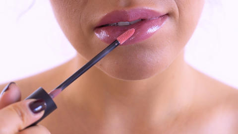 Woman paint lips with lipgloss at white background Footage
