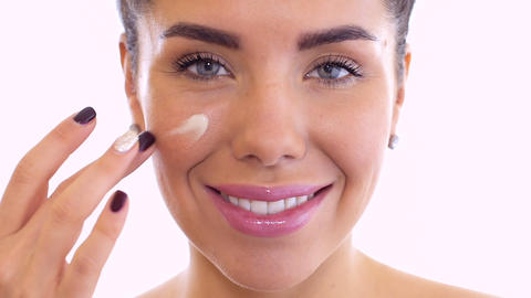 Beautiful woman moisturizes face with cream Footage