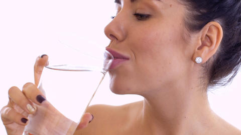 Beautiful young woman drinks water at white background Footage