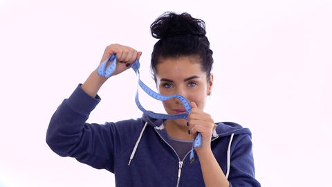Beautiful woman plays with measure tape at white background Footage