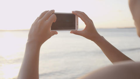 Tourist taking photograph of sunset on beach Live Action