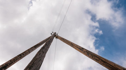 A wooden electric pole against a background of clouds. Time Lapse Footage