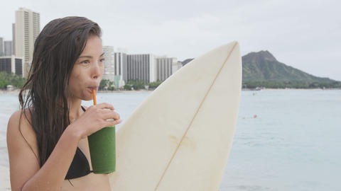 Healthy lifestyle woman surfer drinking green vegetable smoothie Live Action