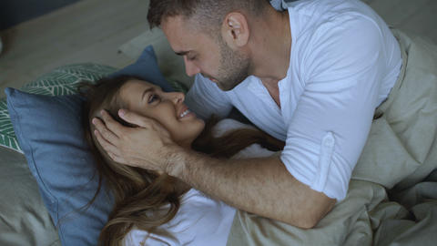 Young beautiful and loving couple wake up at the morning. Attractive man kiss Footage