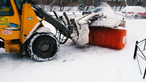 Snowblower with the sweeper brush cleans snow on the road, 4K Footage