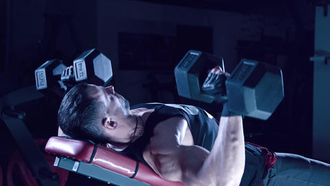 Brutal man shakes his chest dumbbells Image