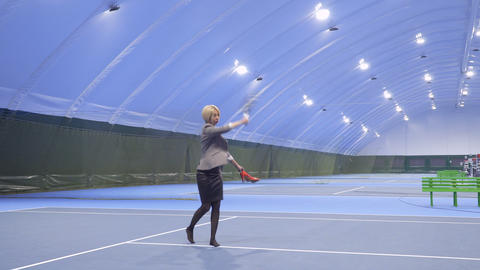 Attractive businesswoman with shoes in hands play tennis at the tennis court Footage