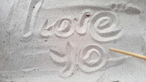 writes the words i love you, on the sand of the beach with a seashell and a GIF