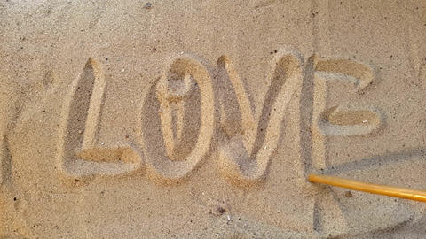 writes the word love, on the sand of the beach with a seashell and a coconut 영상물