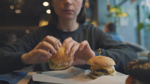 Woman eats a hamburger in a cafe Footage