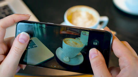 Girl makes a photo of coffee on a smartphone in a cafe close up Live Action