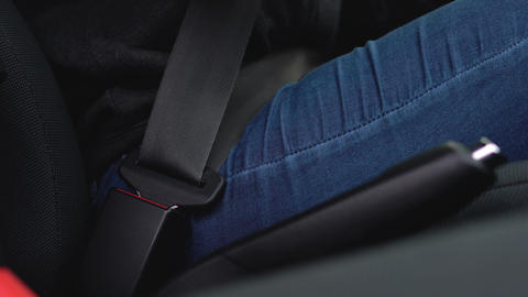 Female hand fastening car safety seat belt while sitting…, Live Action