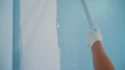 Painter paints the walls in blue color Archivo