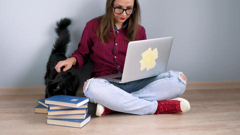 Beautiful girl using laptop and stroking a black cat while sitting on the floor ビデオ