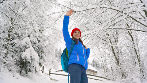 Woman climbs on a snow-covered mountain, turns around, smiling and waving to Footage