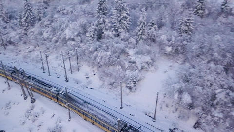 Aerial view of the train going through the mountainous terrain in winter Footage
