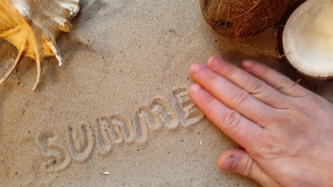 writes the word summer, on the sand of the beach with a seashell and a coconut Footage