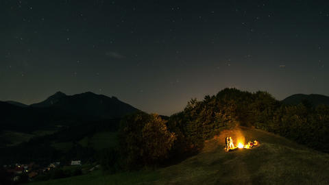 People sitting around campfire at starry moonlight night time lapse Footage