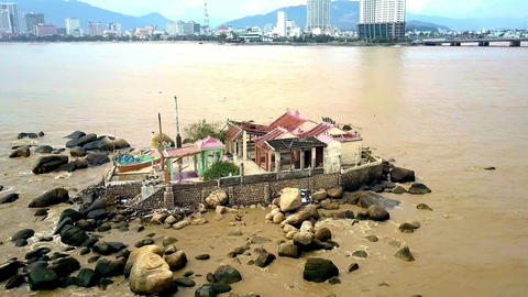 Temple on Rocky Island at Sea against Resort City Hills Image