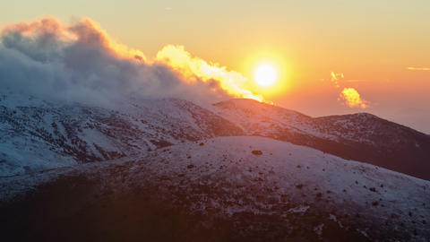 Sunset over snowy mountains time lapse. Frosty colorful evening clouds Footage