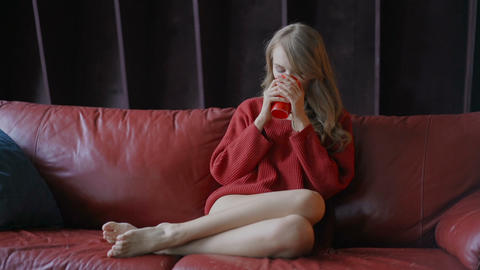 Pretty young woman sitting on red sofa and enjoying morning coffee Footage