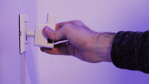 Man insert unplugs repeater from electrical socket on the wall. The device help Live Action