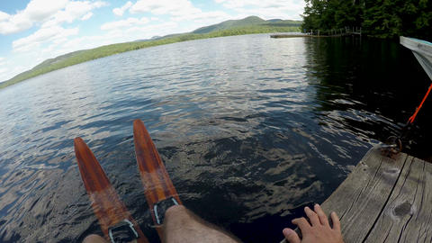 POV of a man wearing wooden waterskis with his feet in a lake sitting on a dock Footage